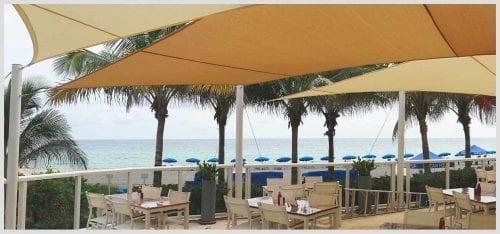 beachside restaurant with yellow sun sail shade